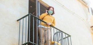 Donna con mascherina parla al telefono sul balcone (foto Shutterstock.com)