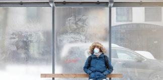 Uomo seduto alla fermata del bus (foto Shutterstock.com)