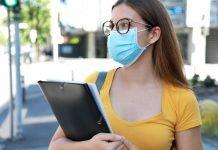 Una studentessa universitaria indossa la mascherina chirurgica (foto di repertorio Shutterstock.com)