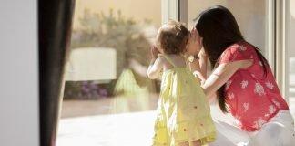 Mamma e figlia guardando attraverso il finestra